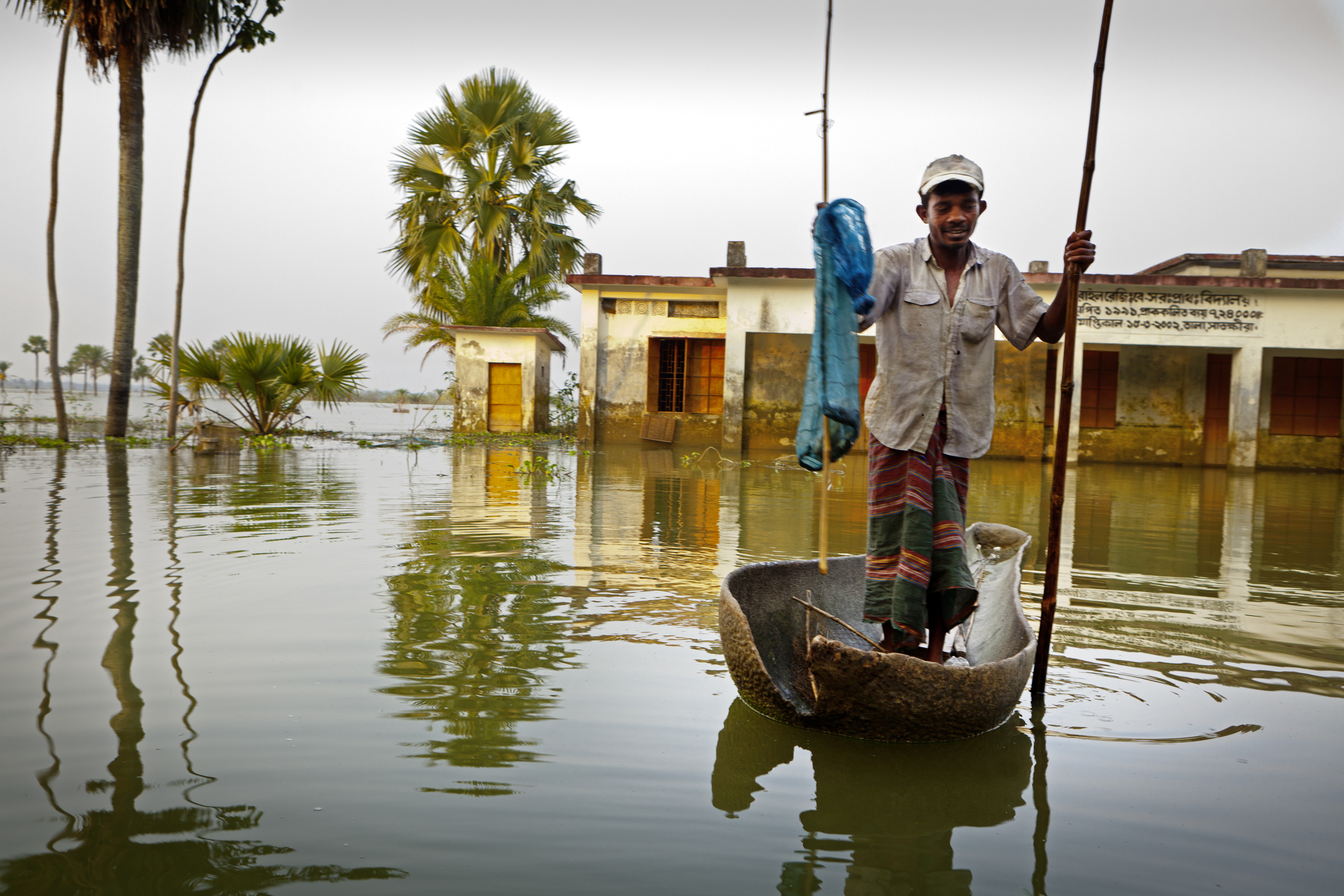 """Fischer mit Holzbooten auf der ueberfluteten regionenin der Naehe von Shyamnagar in Sued - Bangladesh. Hier sind die sind die Auswirkungen des Klimawandels besonders zu spüren Die Partnerorganisation von """"Brot für die Welt"""" CCDB (Christian Commission for Development in Bangladesh) fördert anpassenden Maßnahmen an den Klimawandel. Ziel ist es, dass die Menschen mit den Klimaveränderungen überleben können. (z.B. durch salzresistentes Saatgut, Regenwasserbehältnisse, Mangovenpflanzungen, Schutzbauten (Shelter), verbesserte Hausbauweise, alternative Einkommensmöglichkeiten). Foto: Frank Schultze / Brot für die Welt"""